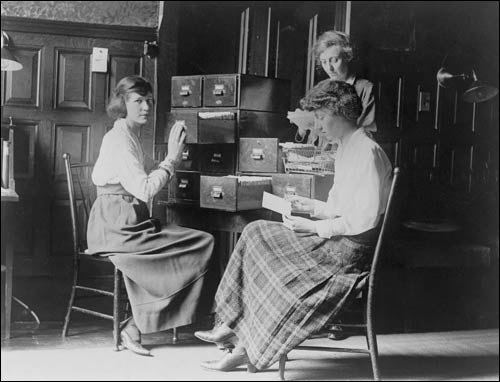 Antique photo of librarians filing cards in a card catalog.