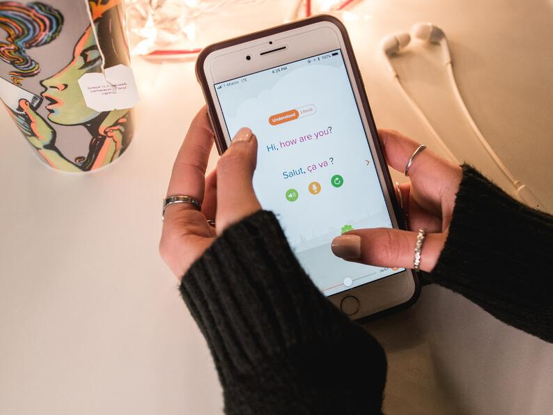 A woman learns French with Mango on her phone.