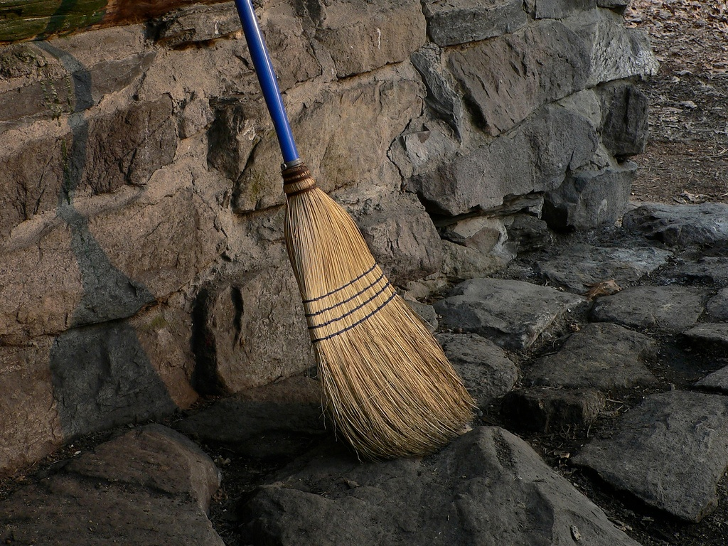 A broom leaning against a brick wall.