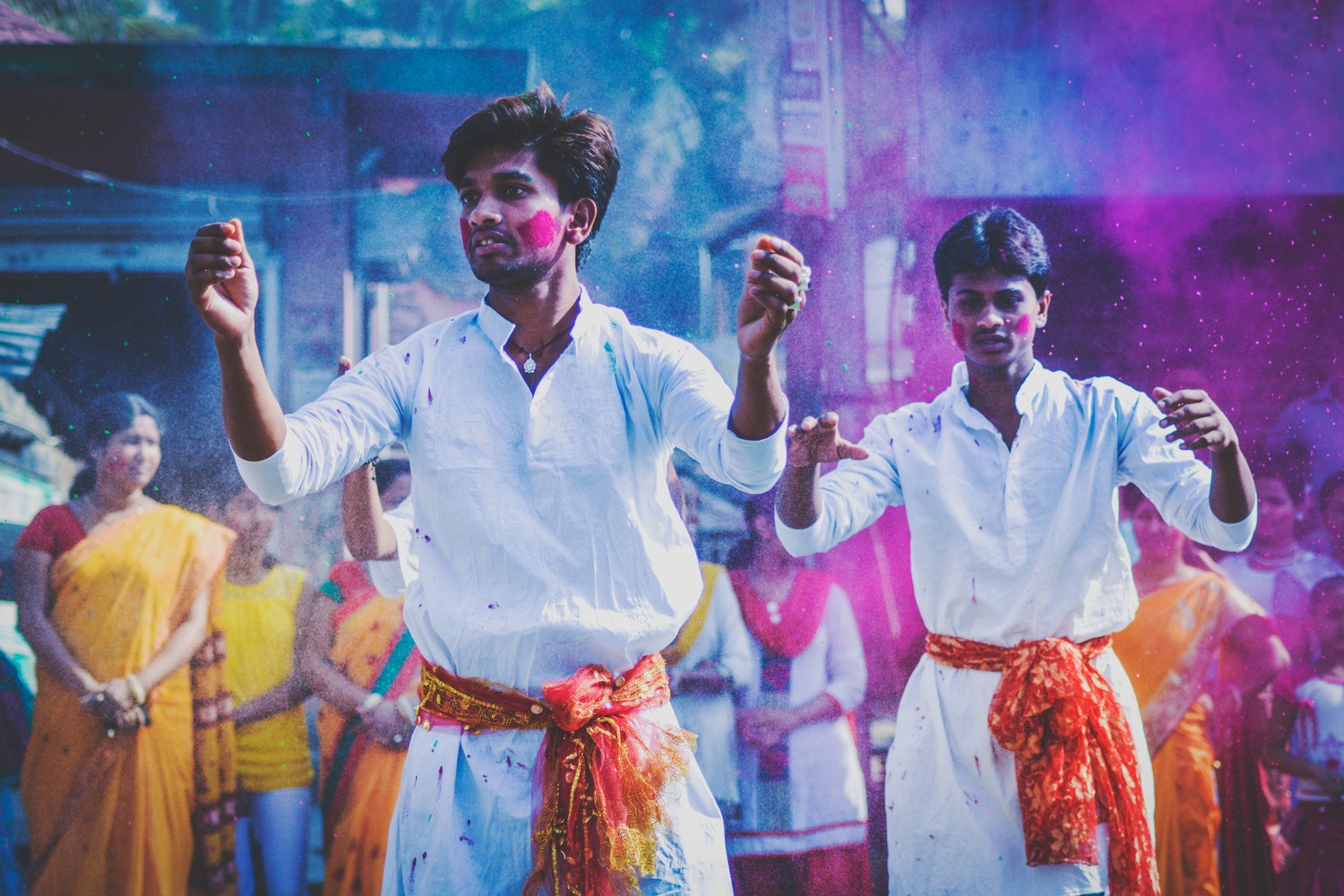 Two men dancing while covered in colors for the Holi festival.