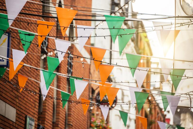 Irish flag garland hanging with lights above the street.