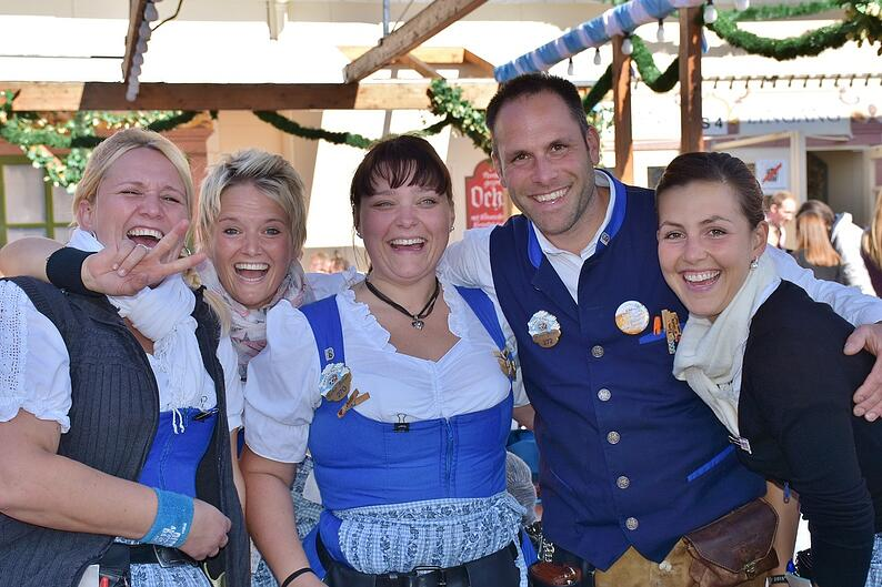Group of friends at Oktoberfest wearing traditional attire.