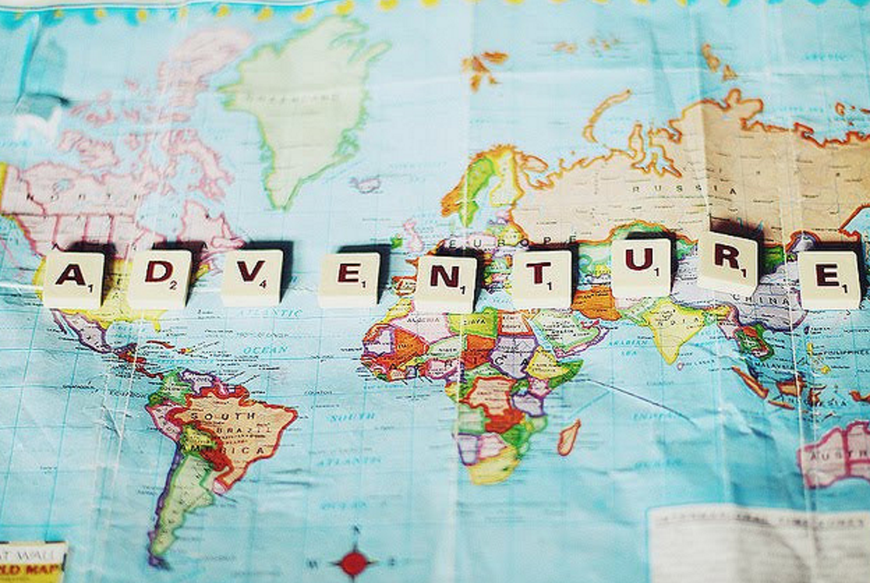 """adventure"" written in scrabble tiles on world map"