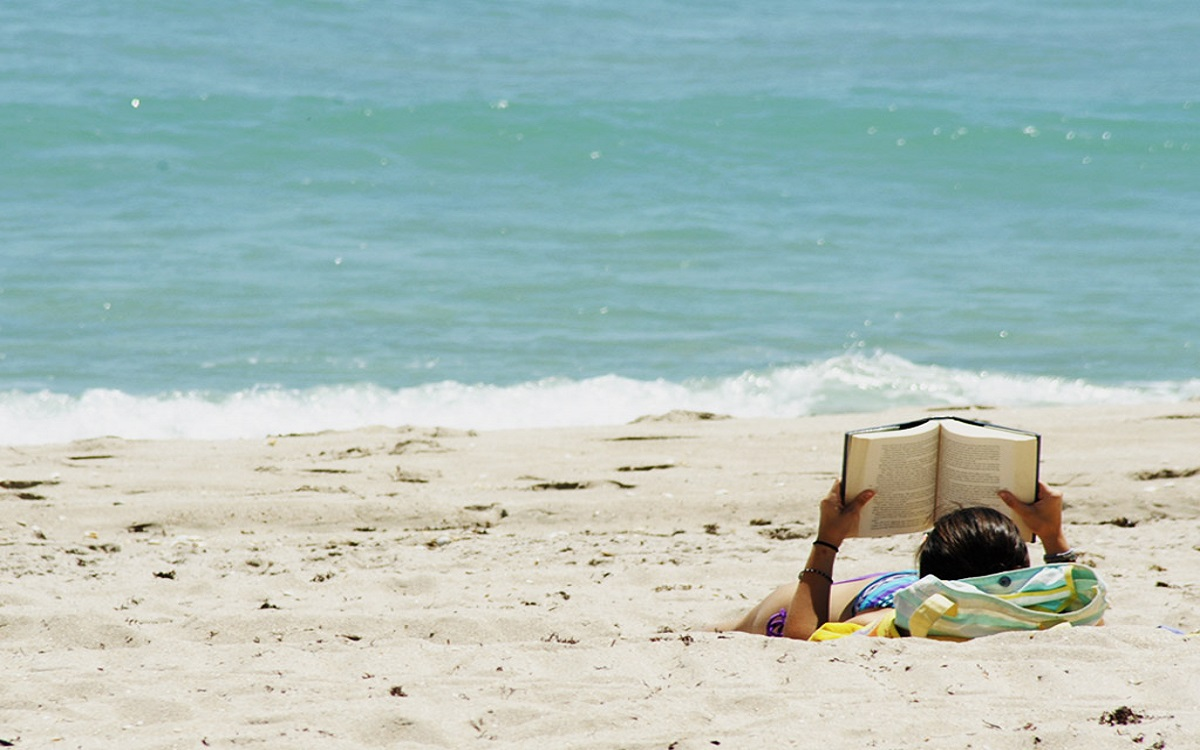 Reading a book on the beach.