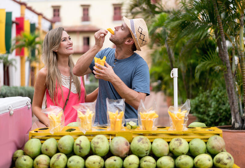 Travelers eating mangos