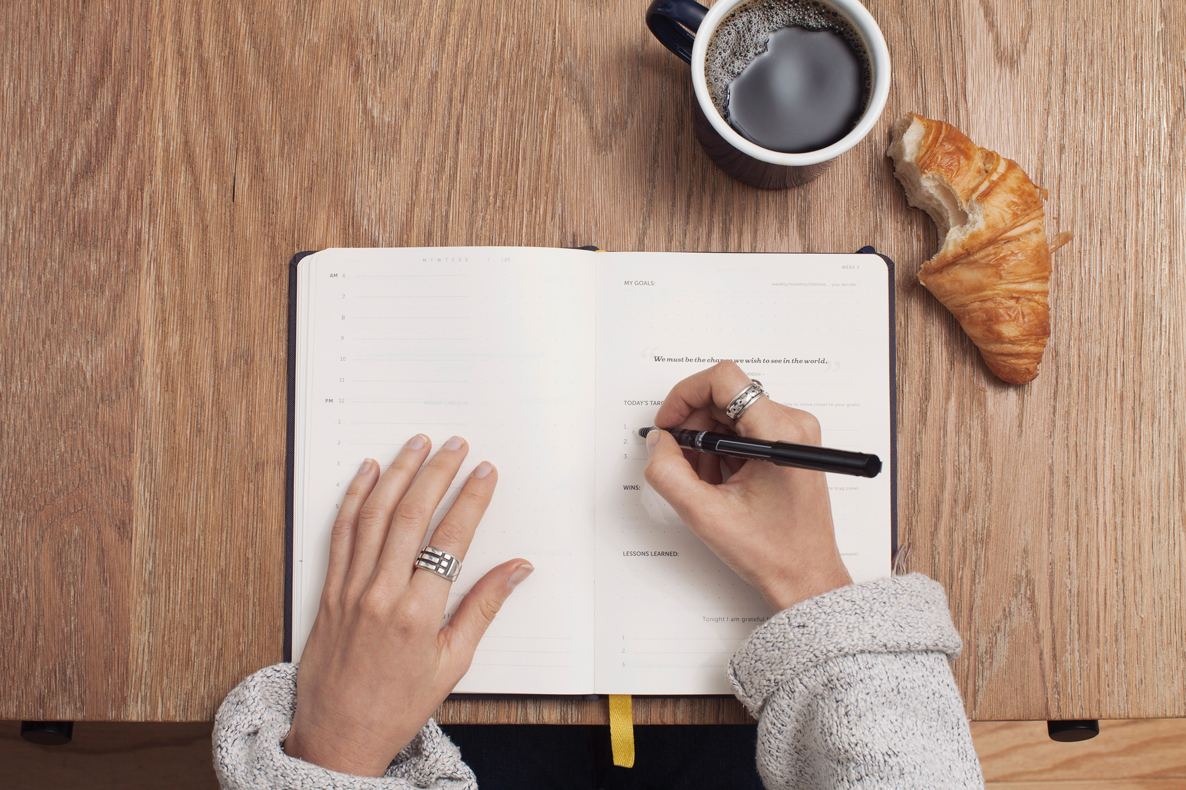 A woman writing in a planner.