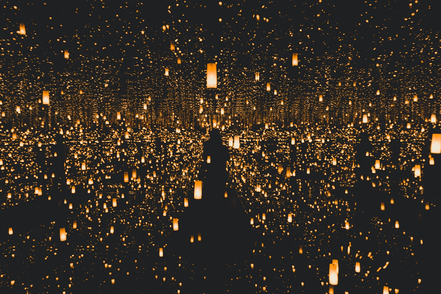 Thousands of floating lights illuminating a dark area.