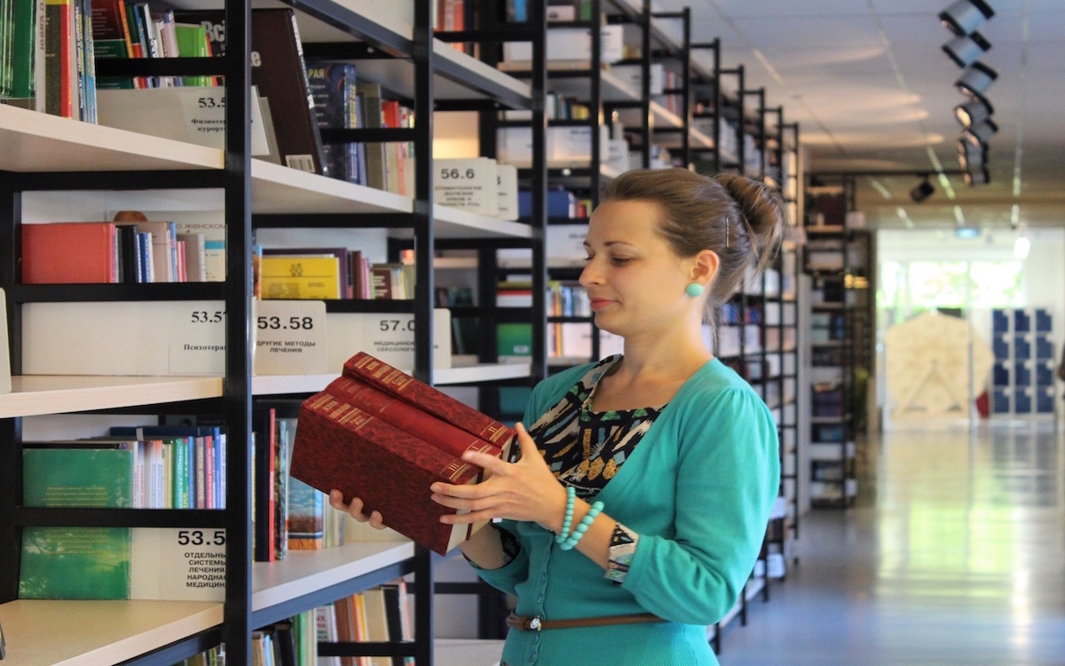 A librarian shelving books in a library.