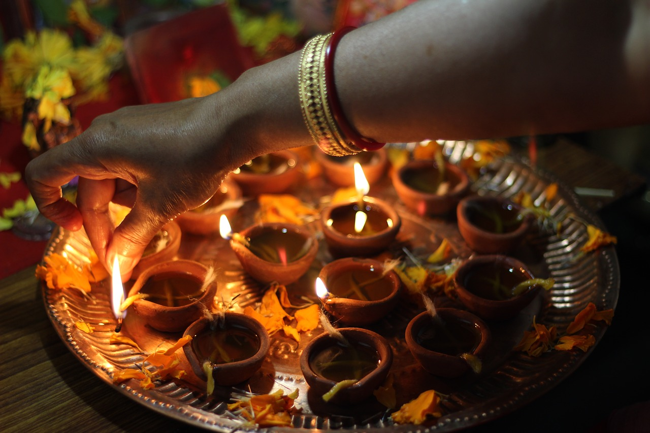 A hand, clad with bangles, lights one of the diyas (oil lamps) for Diwali.