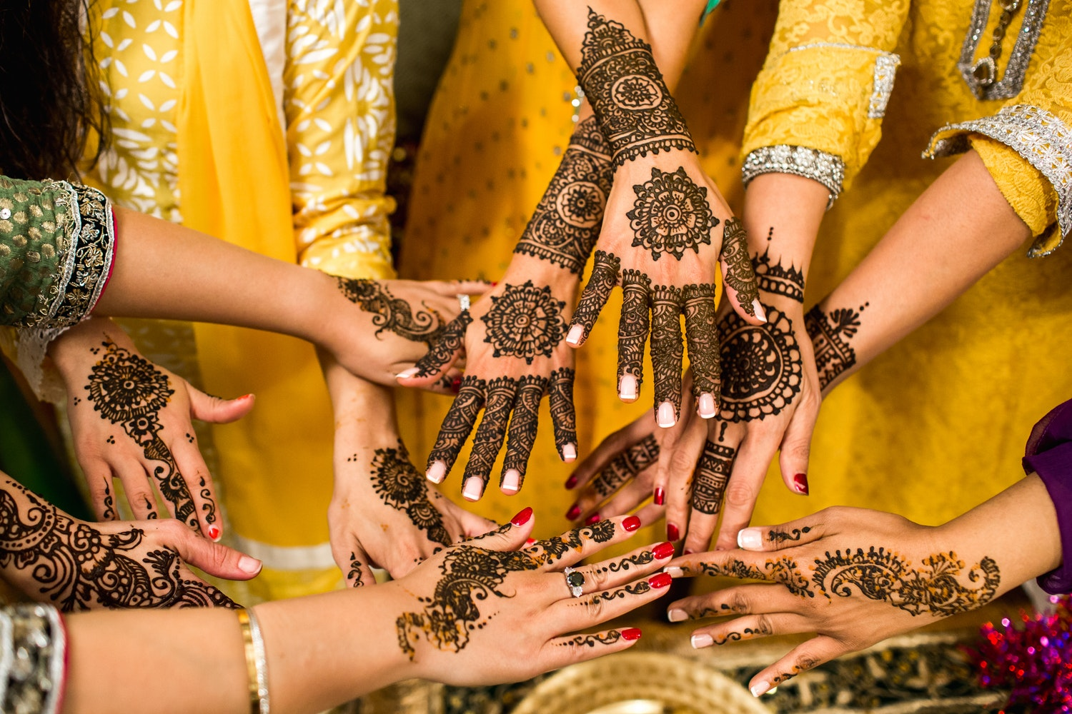Multiple hands decorated with henna.