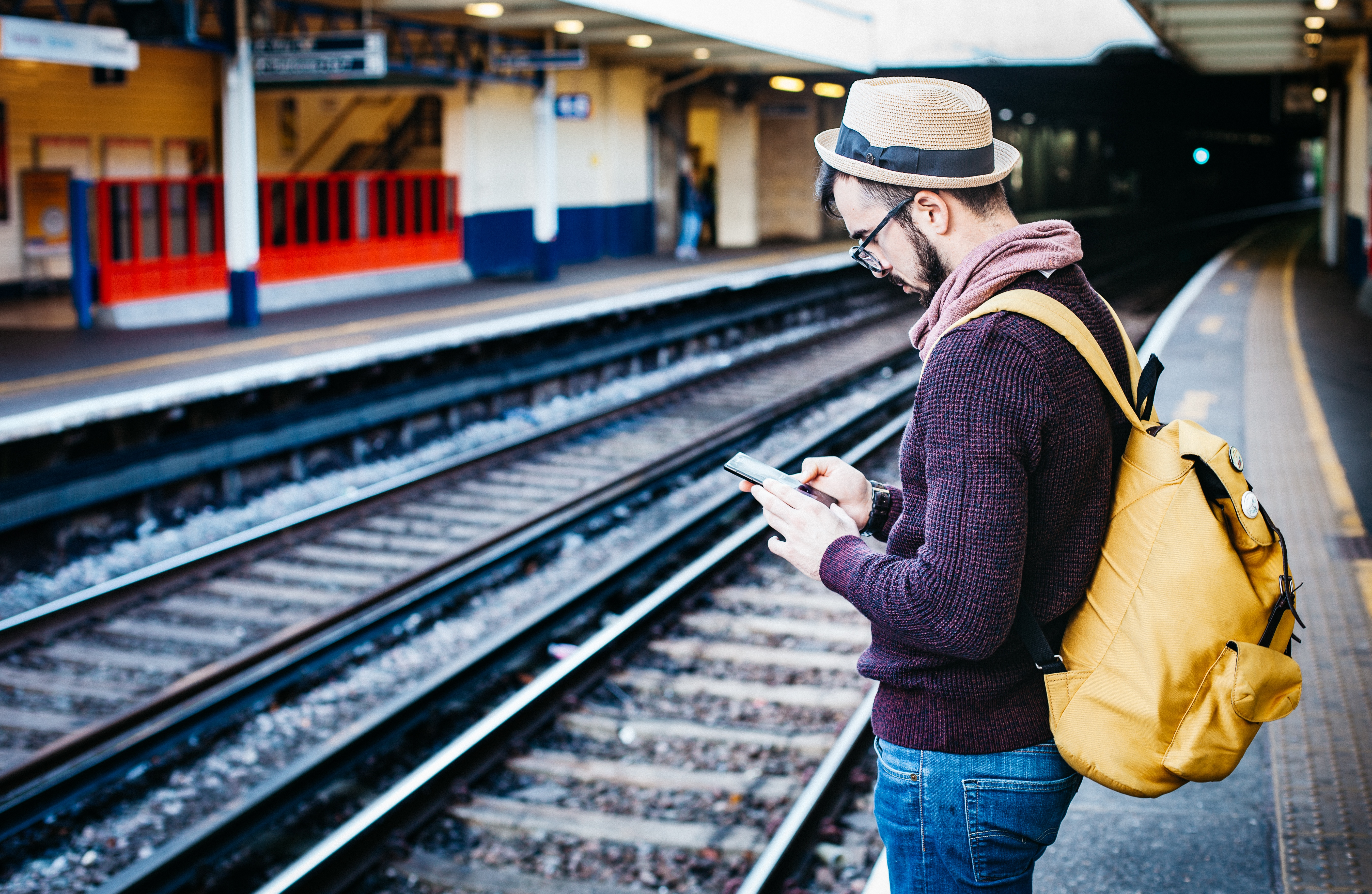 A person on their phone at a train station.