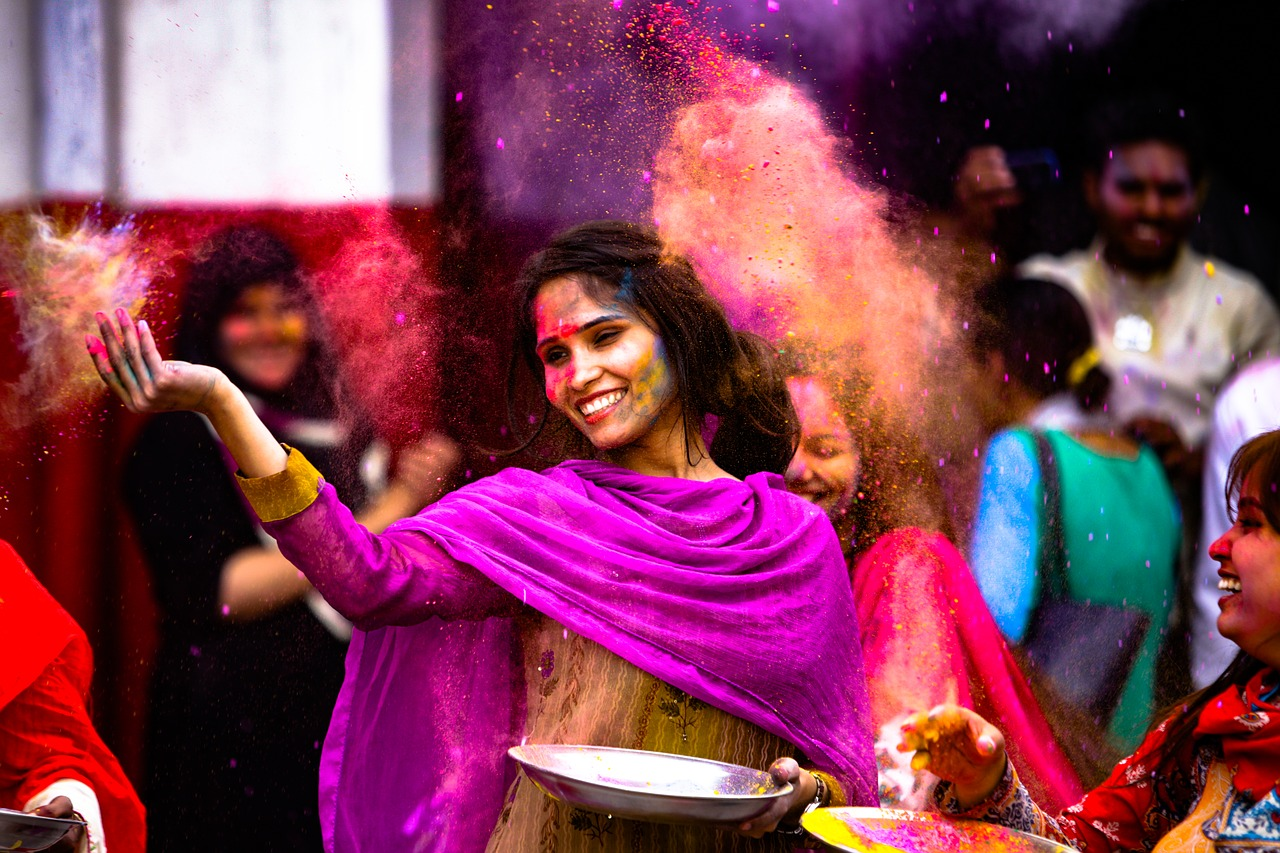Woman happily throwing colors in the air during a Holi celebration.