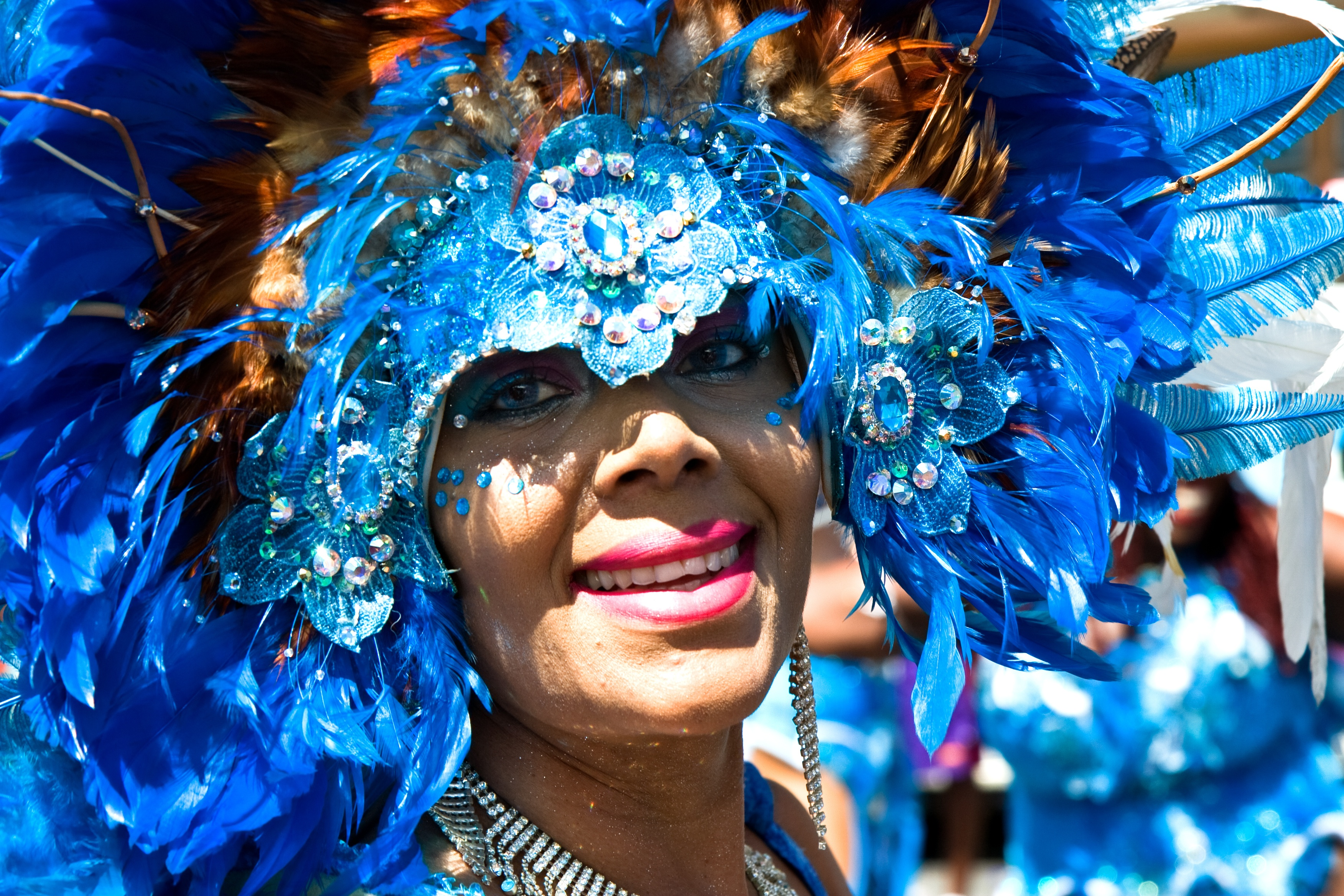 Woman wearing a blue headdress with feathers for Carnaval.