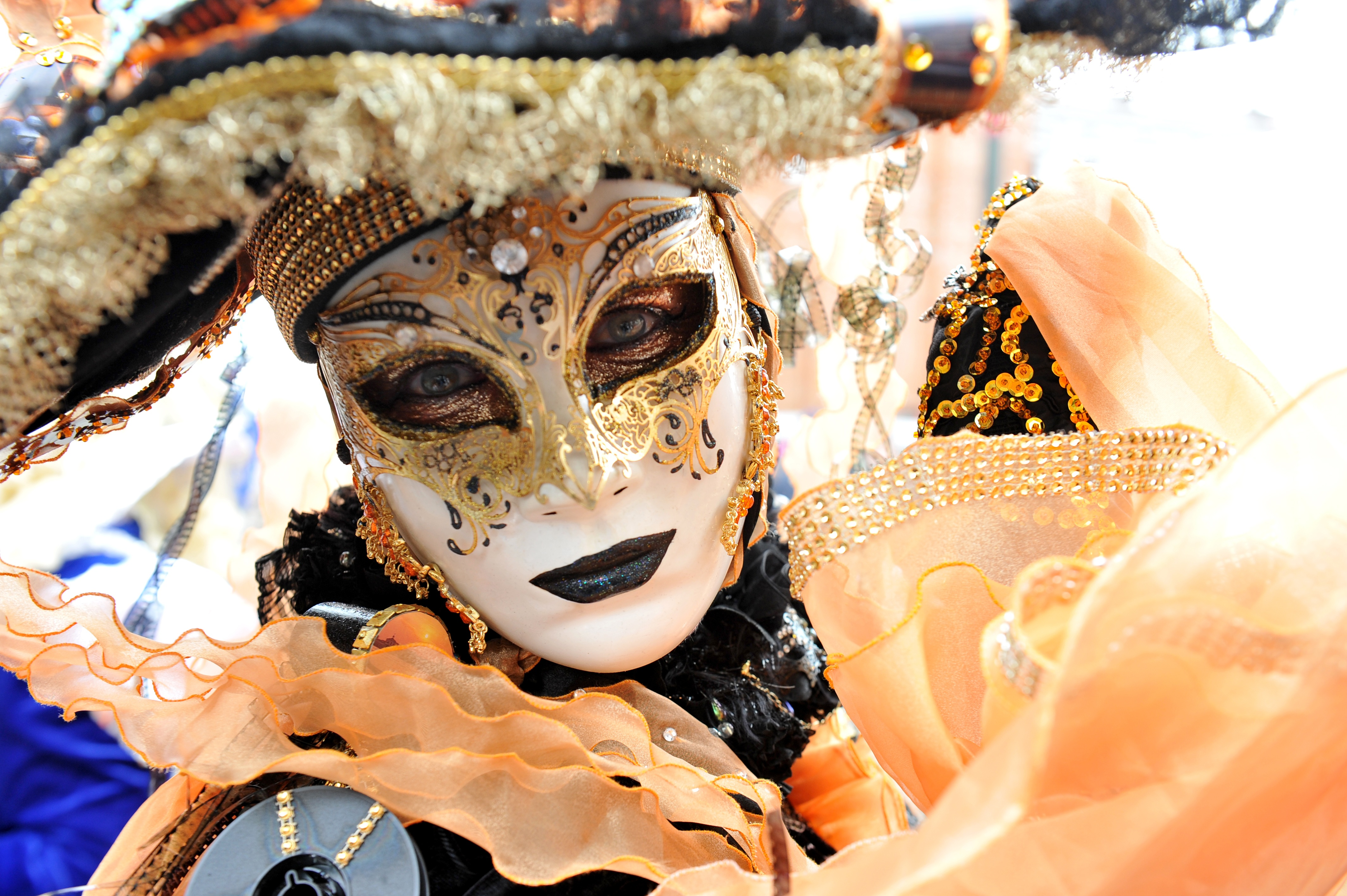 A woman wearing a white and gold Venetian mask for the Carnival of Venice.