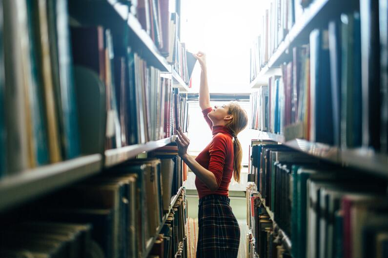 A woman searching for a book in a library.