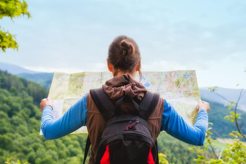 A woman reading a map while hiking in the mountains.
