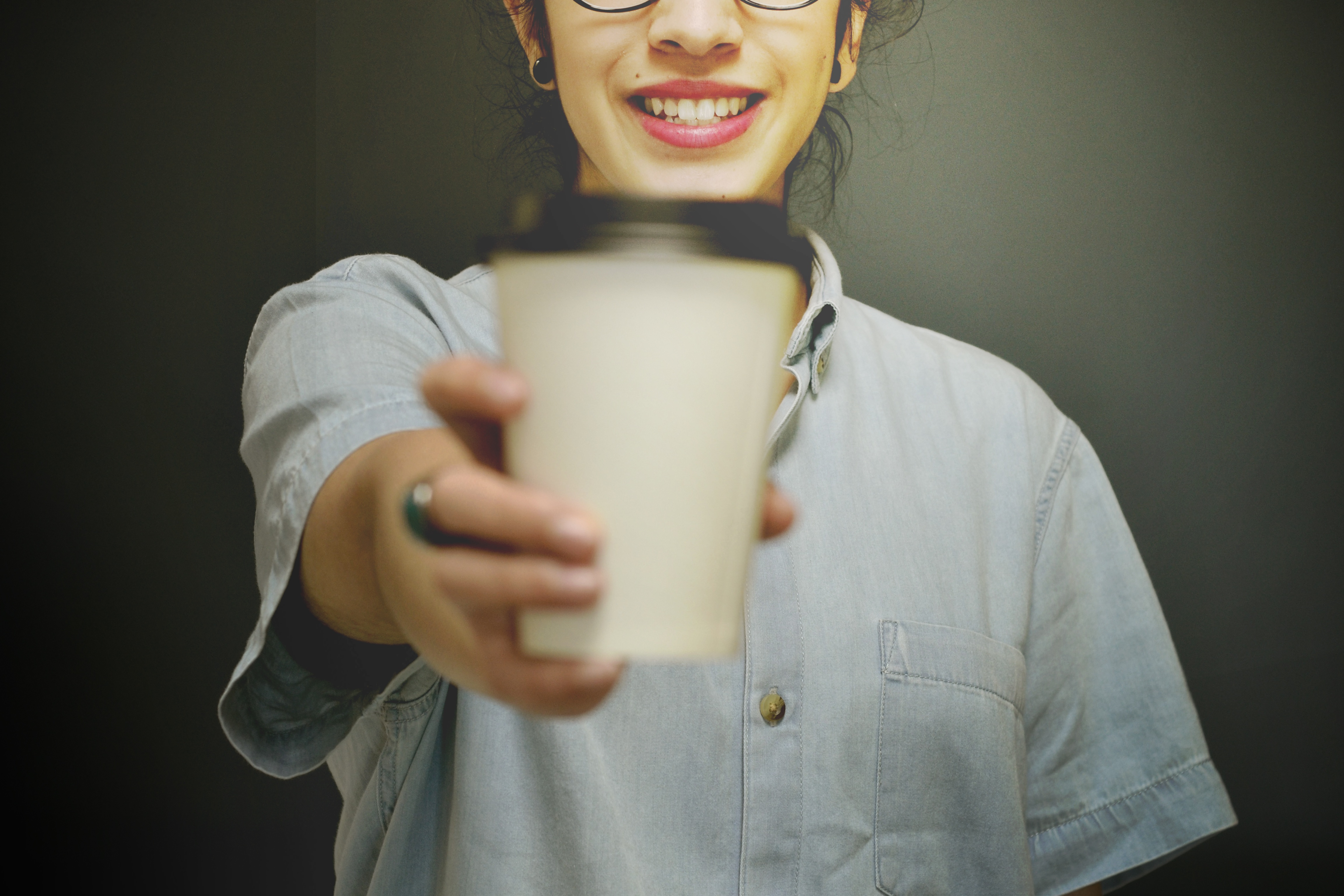A smiling person holding a coffee.