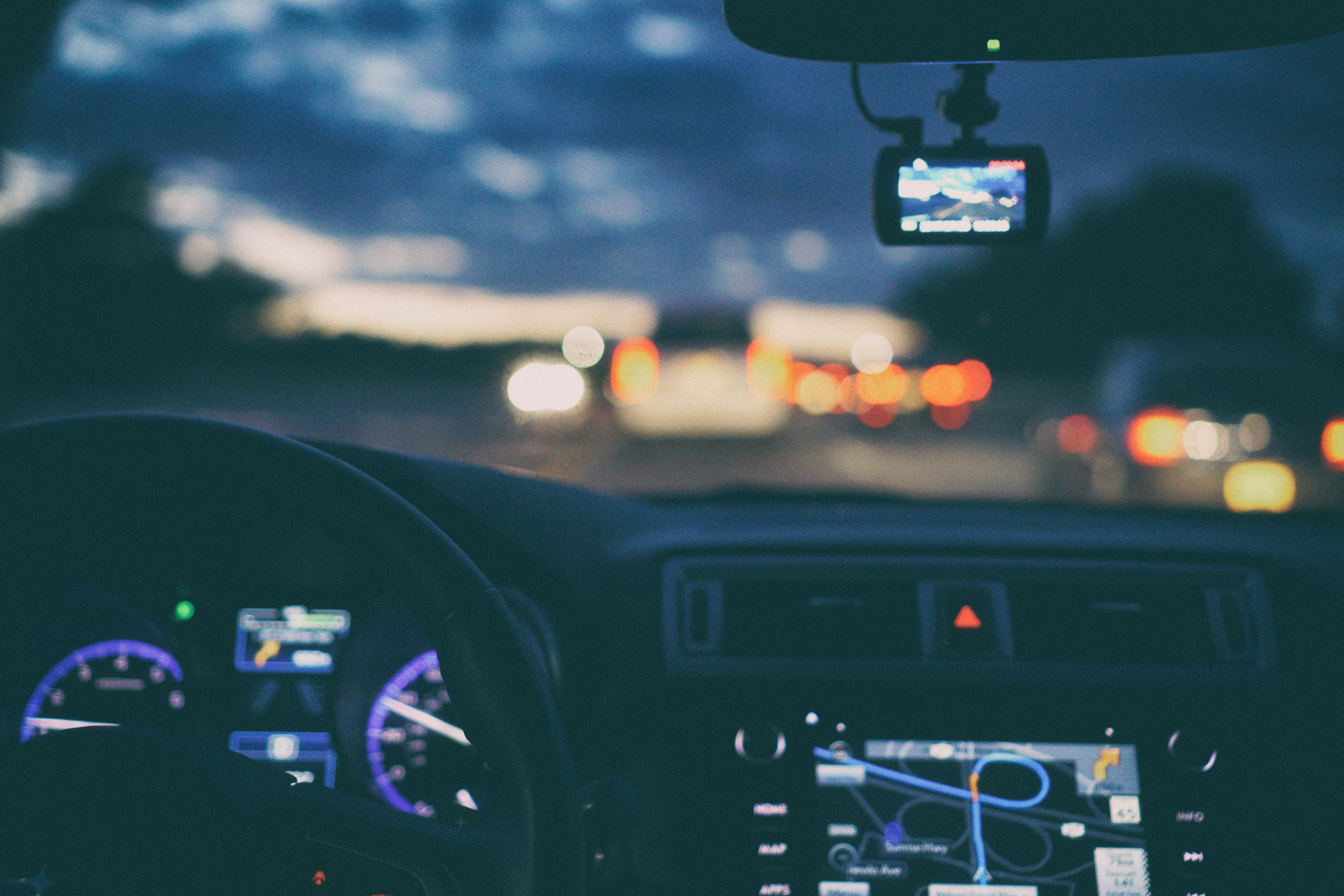 Blurry image of car dashboard and windshield at night.