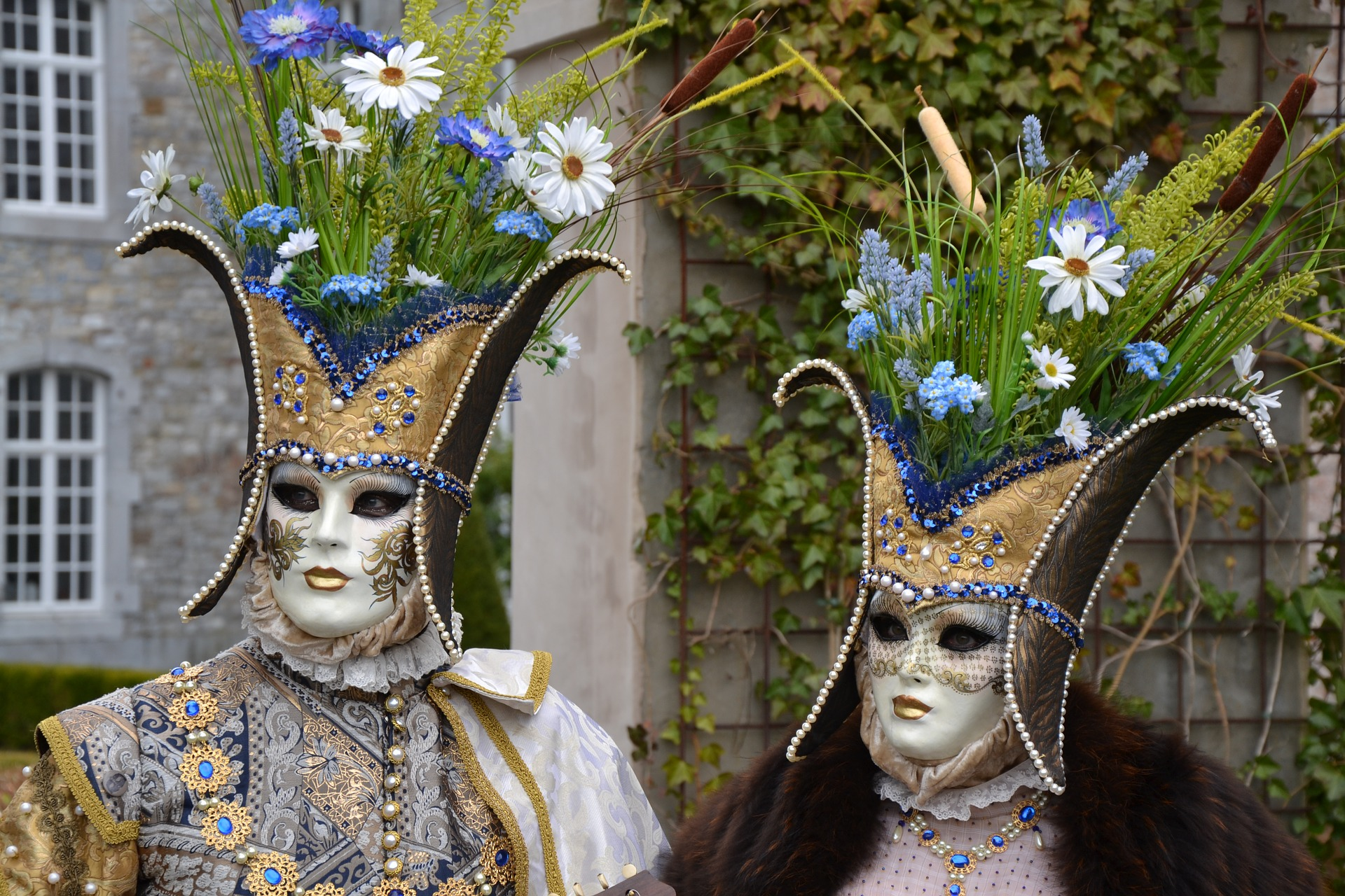A couple wearing ornate Venetian costumes and masks for the Carnival of Venice.