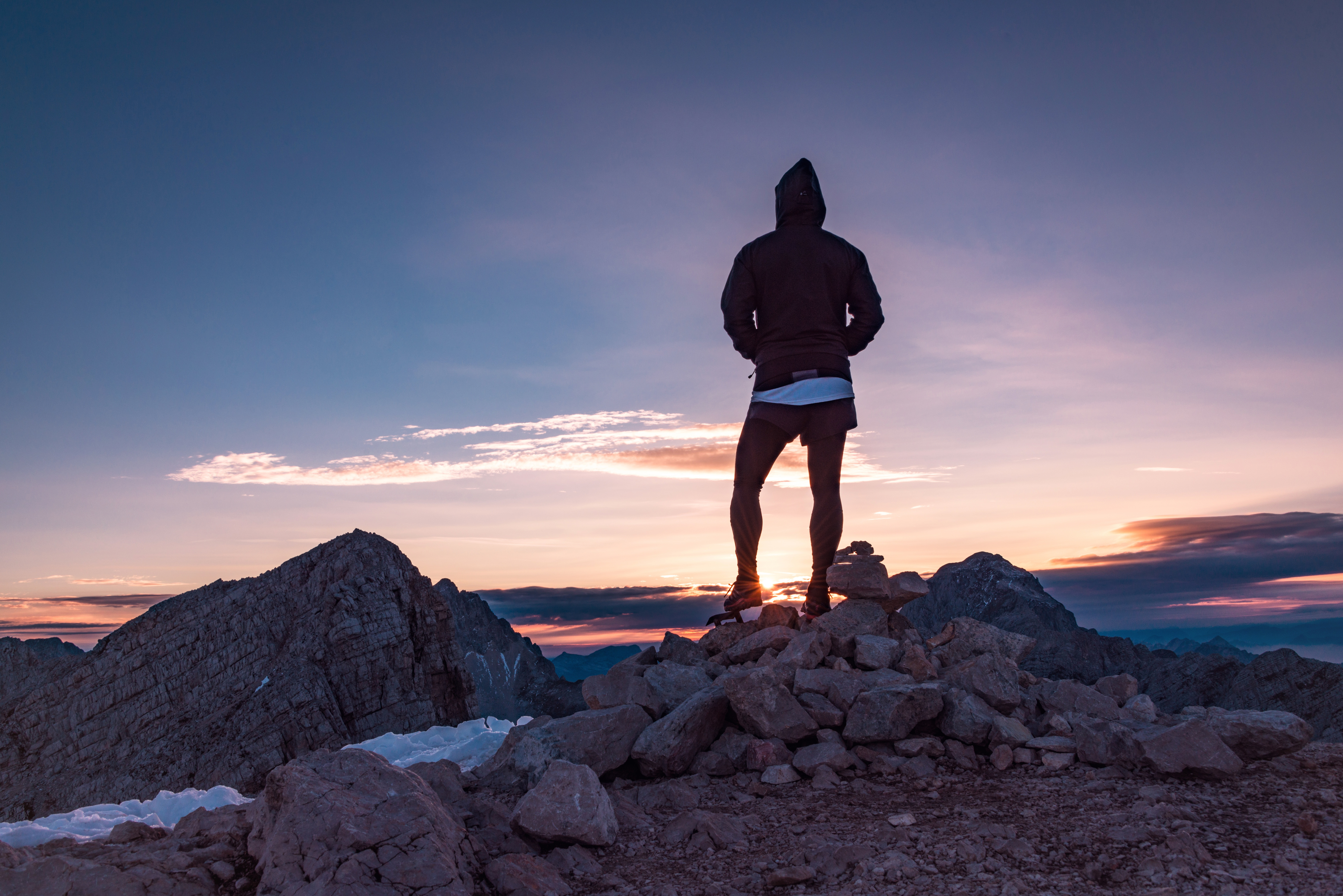 A hiker standing on top of a mountain.