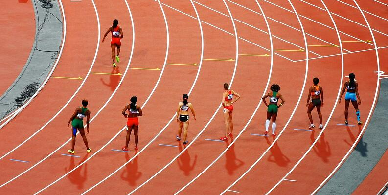 Track and Field athletes line up on the track before a race.