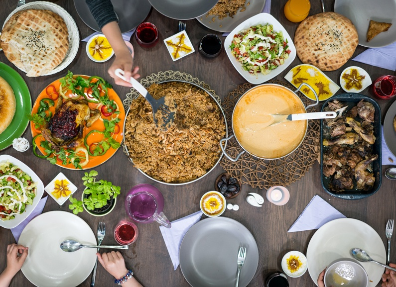 An iftar table full of common Ramadan foods from different Arab countries.