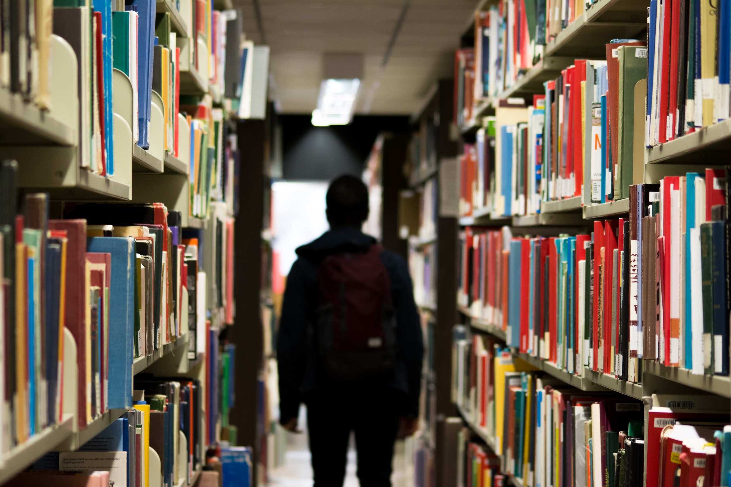 A student walking through the shelves of a library.