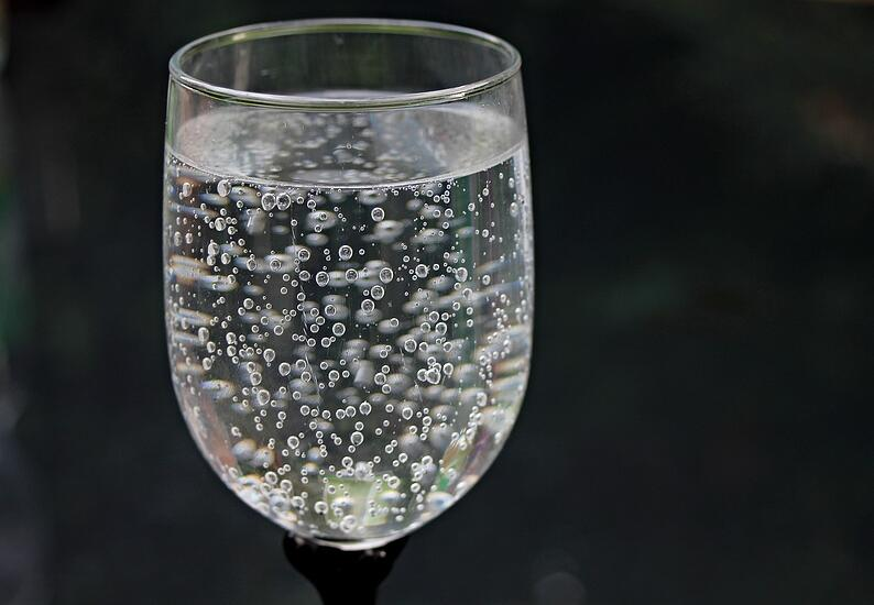 Sparkling water in wine glass in front of black background.