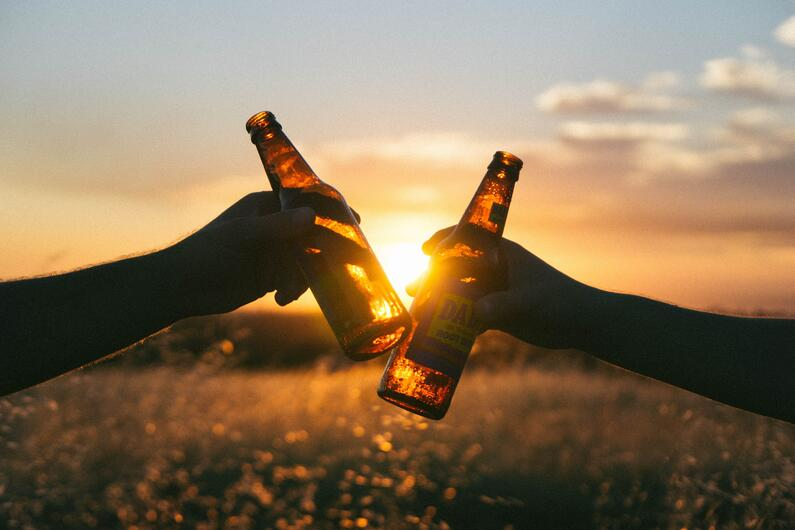 Beer bottles clinking in front of sunset in a field.