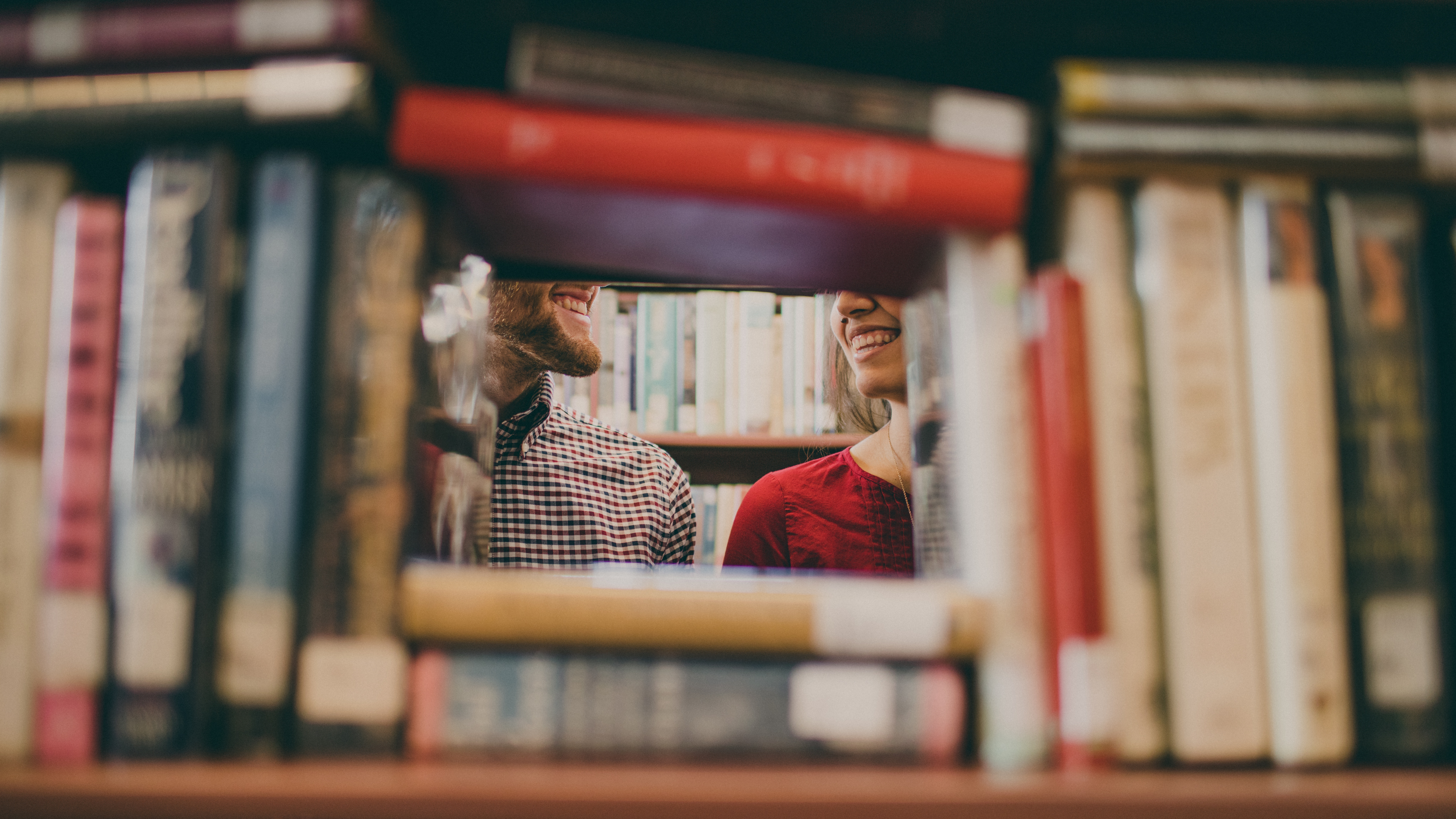 A couple behind a bookshelf.