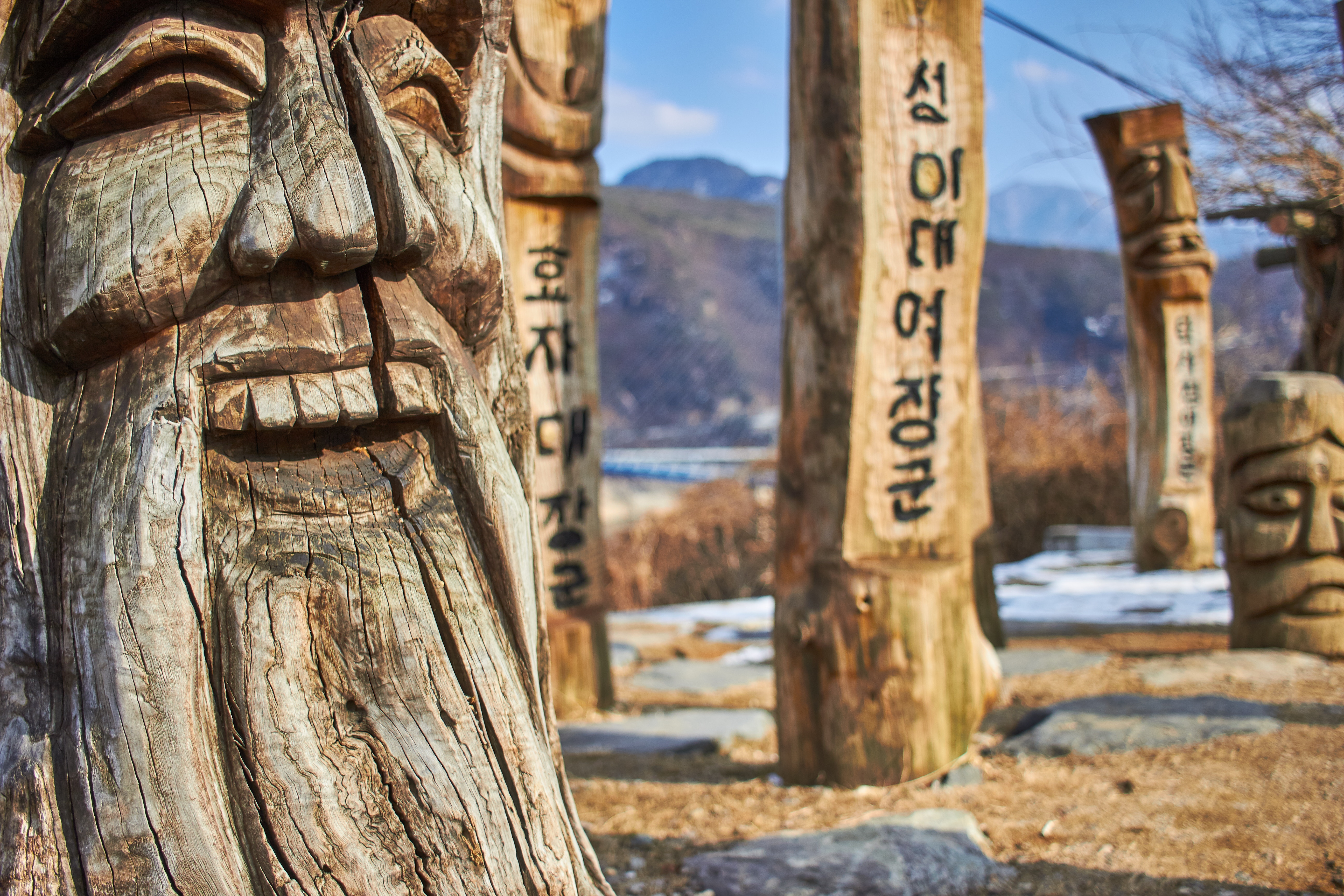 Faces carved into wood with Hangul written on the sides.