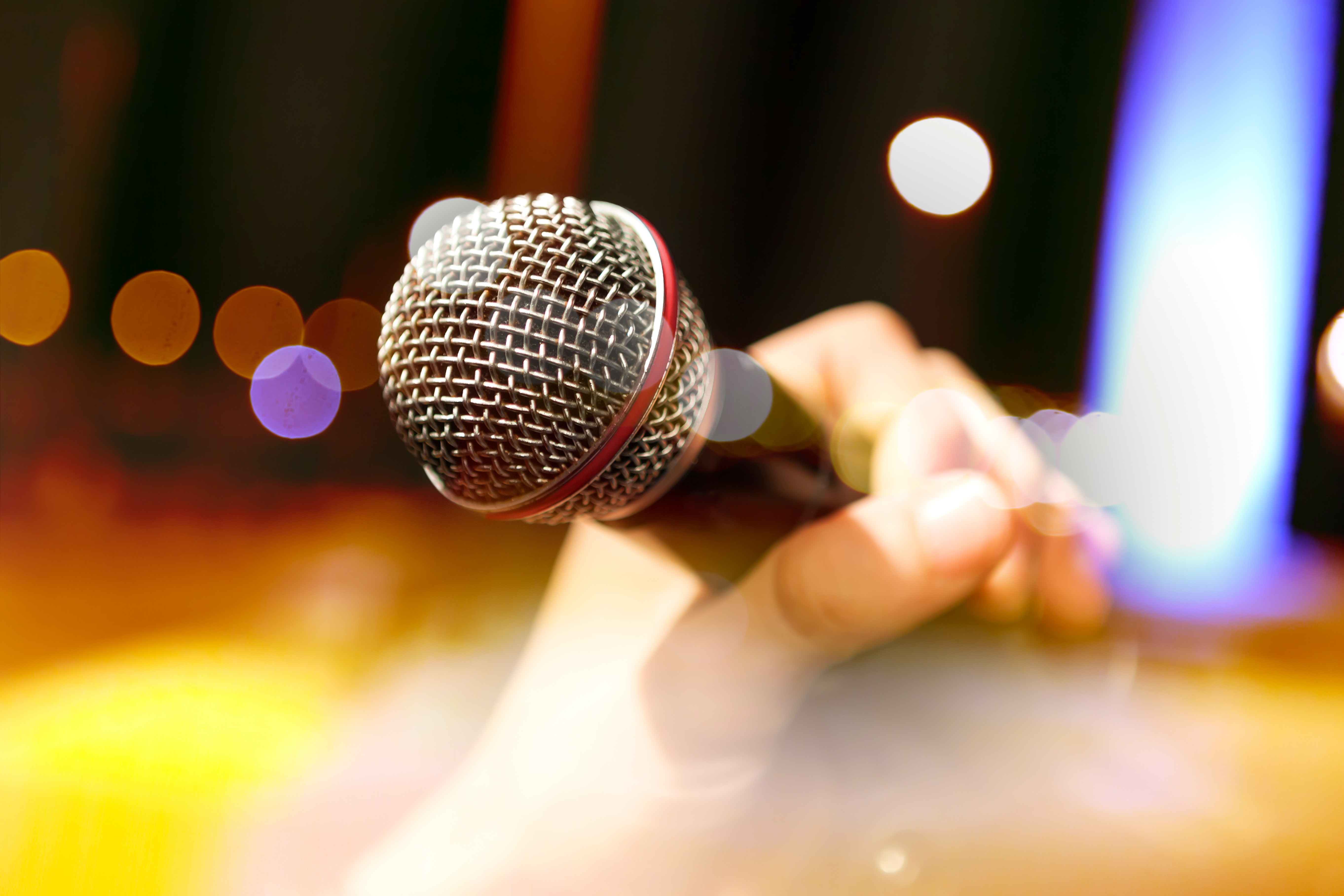 A hand holding a microphone.
